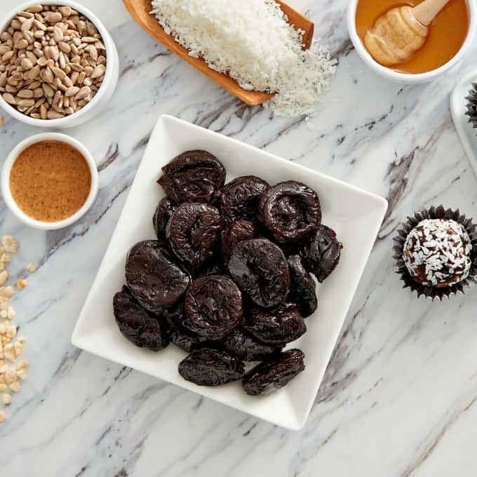 Prunes on a plate with ingredients to make power balls recipe