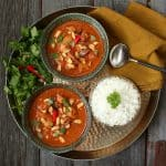 Peanut Butter Chicken Curry - A gold tray holds two bowls of bright brown curry, rice, cilantro and Thai red peppers.