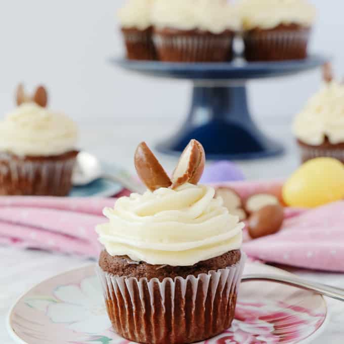 Chocolate cupcake with white frosting with 2 halves of chocolate egg on top, more cupcakes in the back cupcakes on the a blue cake stand.