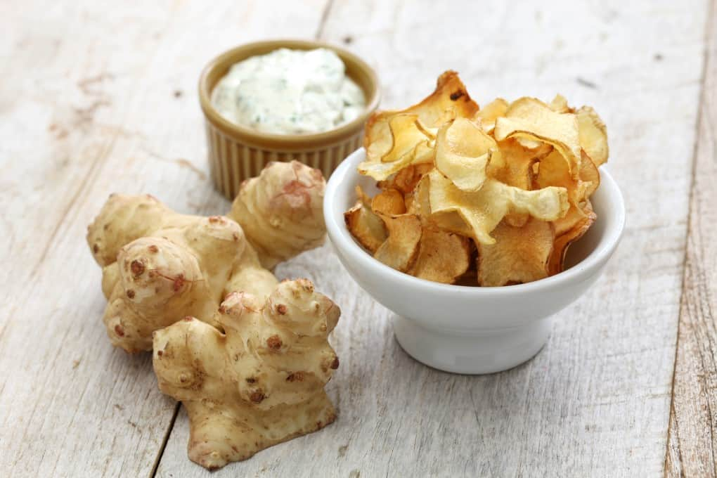 A sunchoke raw and a bowl of sunchoke chips with dip