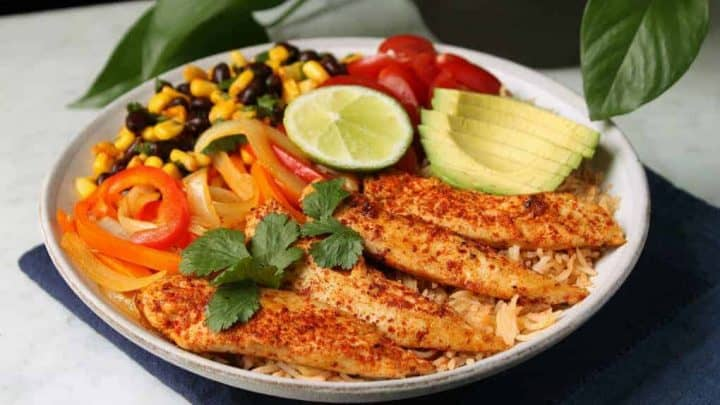 Healthy Chicken Burrito Bowl - A low white bowl filled with healthy vegetables, bean salad, avocado, rice, and chicken tenders.