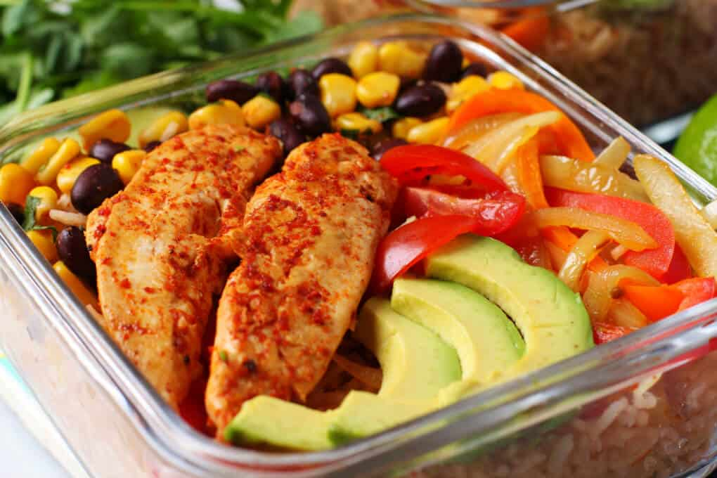 Healthy Chicken Burrito Bowl - Close up of a glass container filled with healthy vegetables, bean salad, avocado, rice, and chicken tenders.