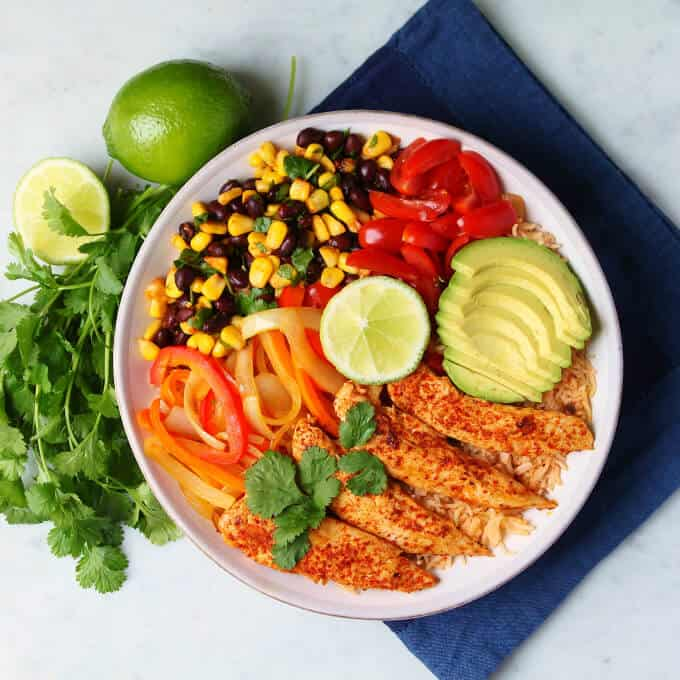 Healthy Chicken Burrito Bowl - overhead photo featuring a bowl filled with healthy vegetables, bean salad, avocado, rice, and chicken tenders.