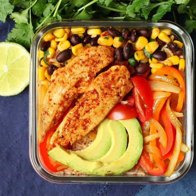 Healthy Chicken Burrito Bowl - overhead photo featuring a glass container filled with healthy vegetables, bean salad, avocado, rice, and chicken tenders.