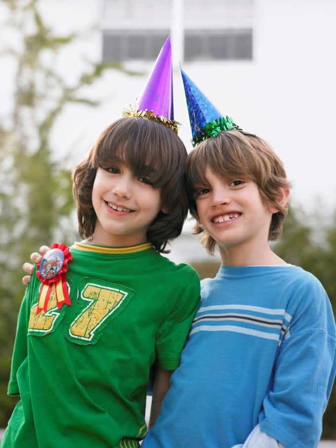 Two boys with birthday party hats