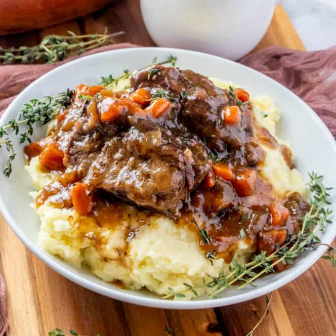 Braised Short ribs in a bowl with mashed potatoes.