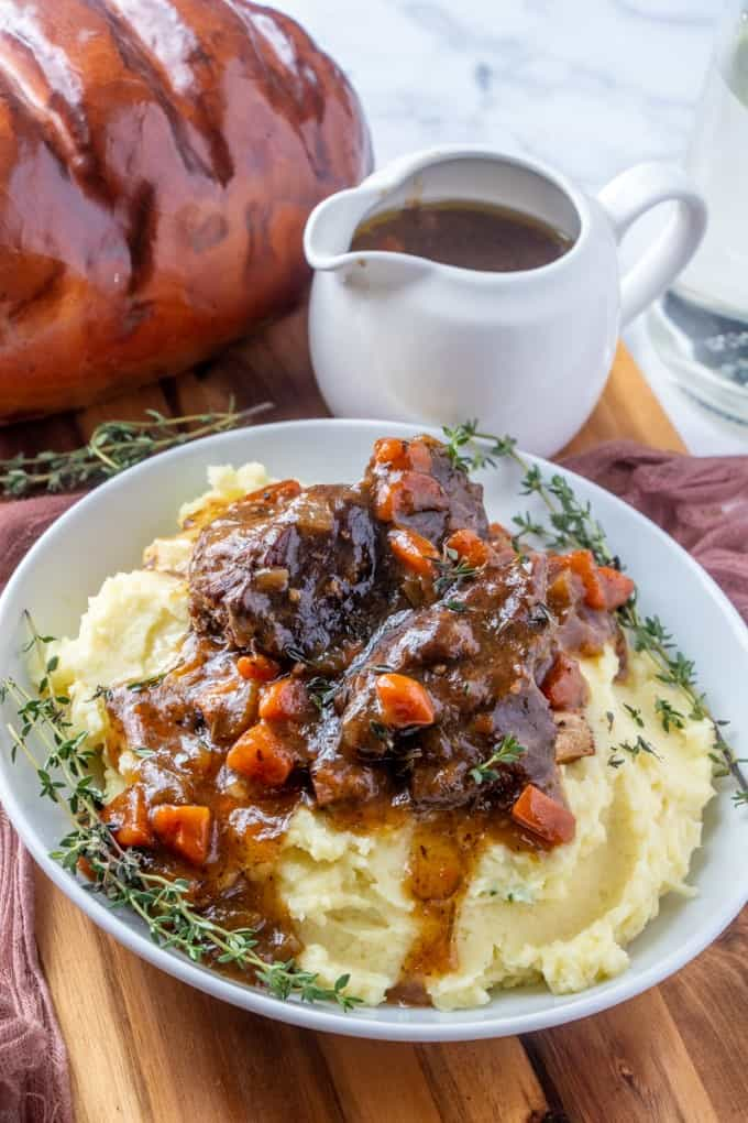 Braised Short Ribs in a bowl with a gravy boat and bread