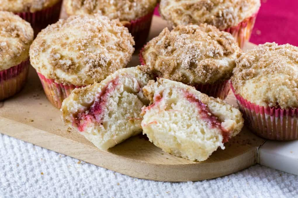 Board of rhubarb muffins with one sliced open