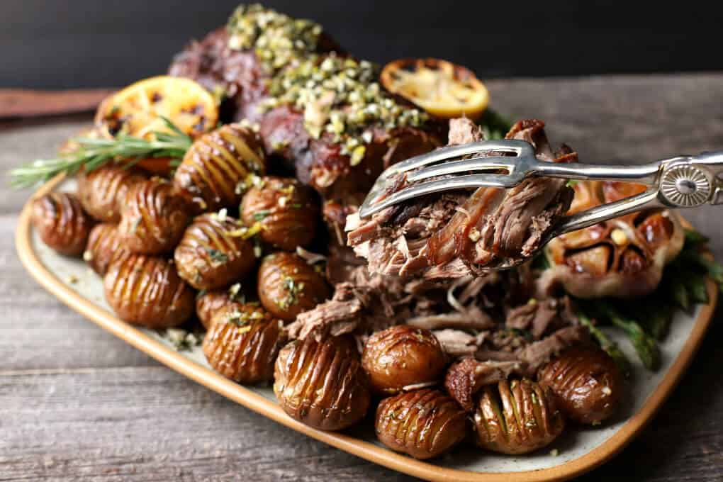 Slow Roasted Boneless Leg of Lamb - A pair of silver tongs holds tender, pulled lamb.