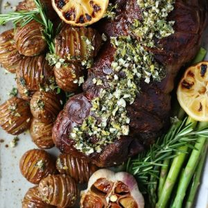 Slow Roasted Boneless Leg of Lamb - overhead view of a platter filled with lamb roast, mini hasselback potatoes, lemons, asparagus, and roasted garlic.