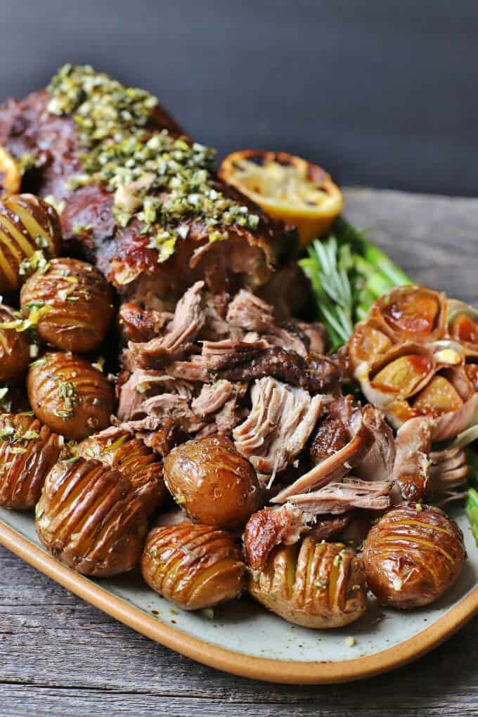 Slow Roasted Boneless Leg of Lamb - a platter filled with shredded lamb roast, mini hasselback potatoes, lemons, asparagus, and roasted garlic.