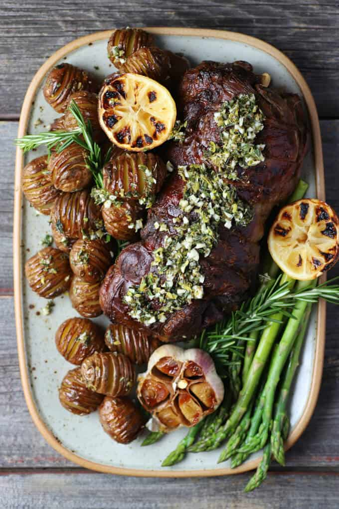 Slow Roasted Boneless Leg of Lamb - Overhead photo of a platter filled with lamb roast, mini hasselback potatoes, lemons, asparagus, and roasted garlic.
