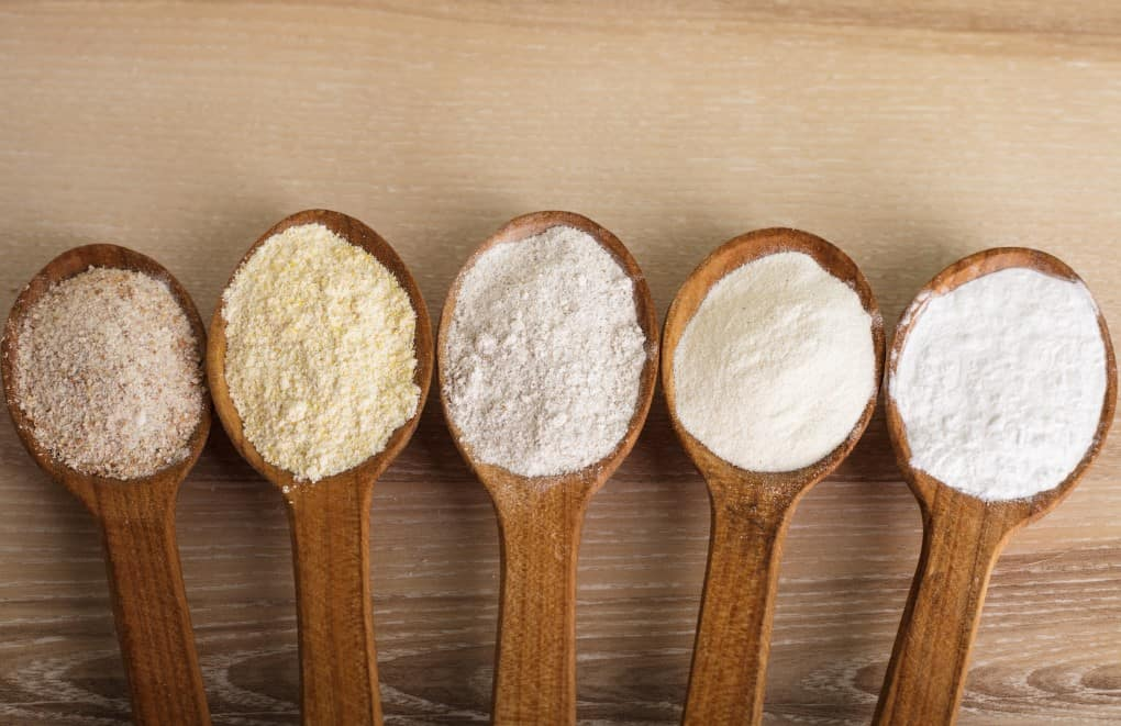 Various types of flour in five wooden spoons