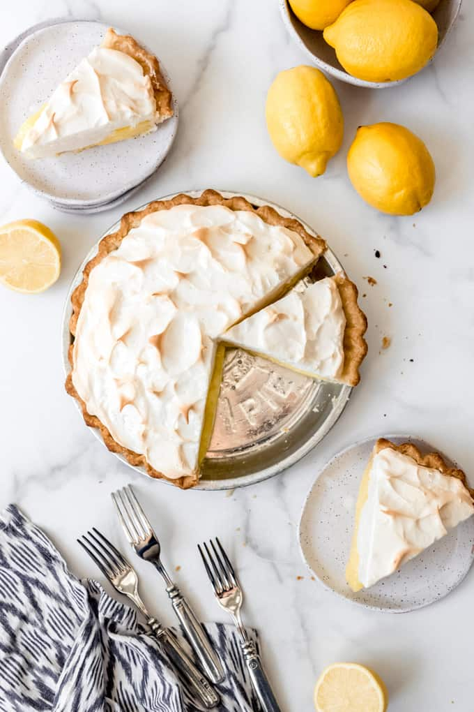 An image of slices of lemon meringue pie on plates beside the remaining pie.