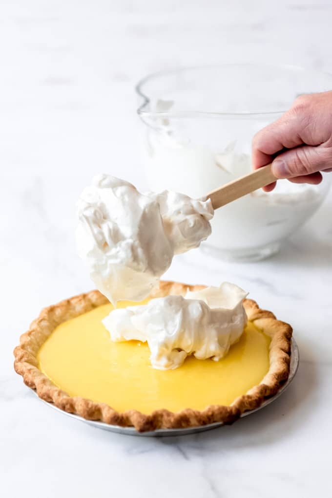 An image of meringue being spread on lemon pie filling.