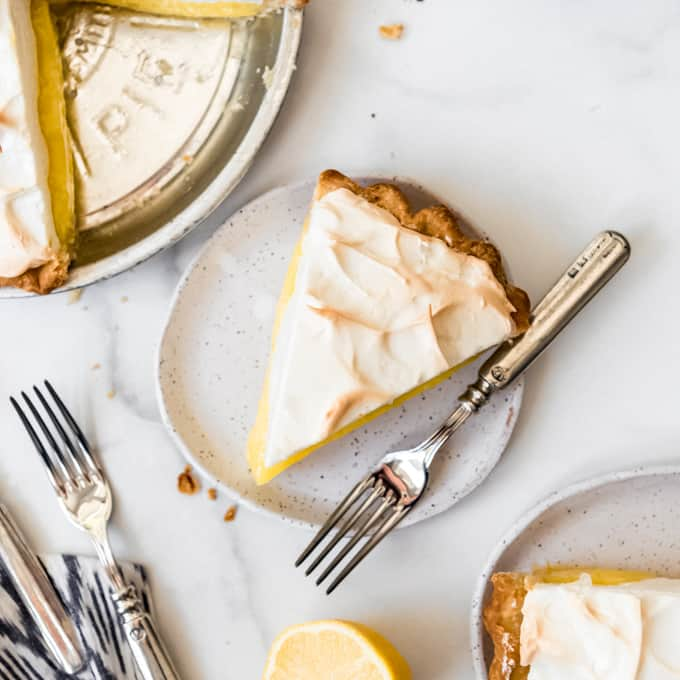 An image of a slice of lemon meringue pie on a plate with a fork.