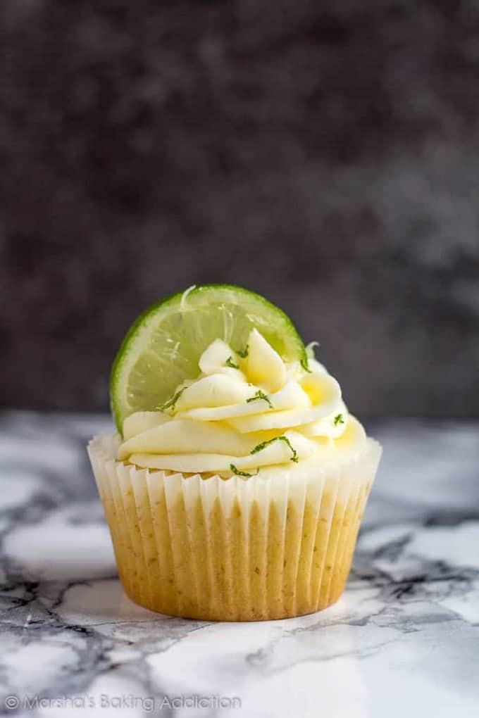 Margarita cupcake with a lime slice in the frosting on a marble table