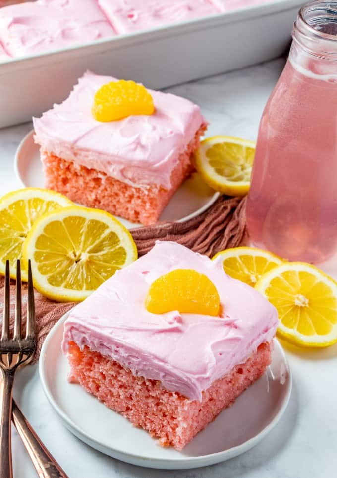 Full picture of two pieces of cake with lemon slices on the counter and bottle of lemonade