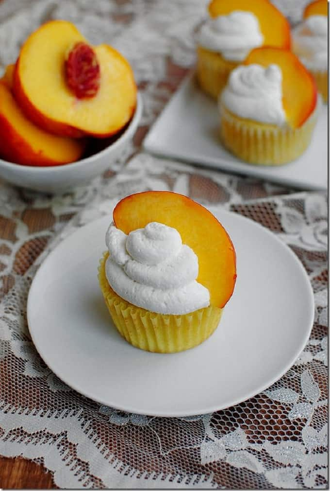 peaches N cream cupcakes on a white plate and a bowl of sliced peaches