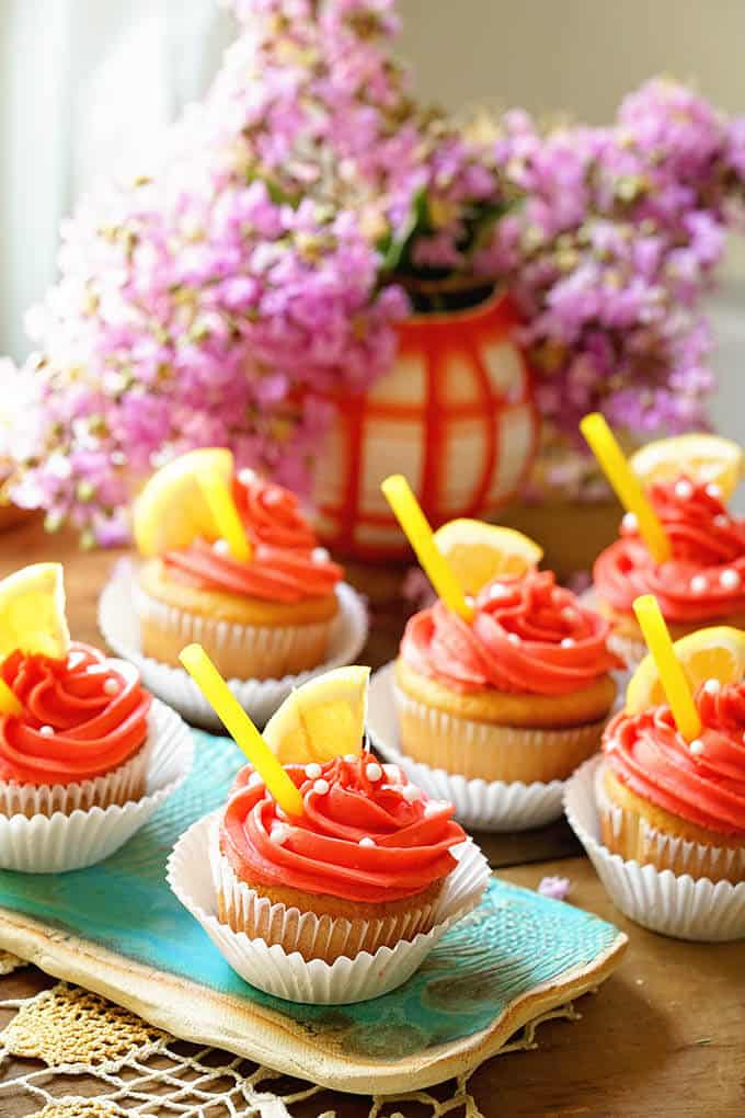 Pink Lemonade cupcakes on a table with flowers in the background