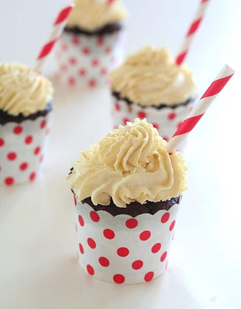 Root beer float cupcakes on a white table with a straw sticking out