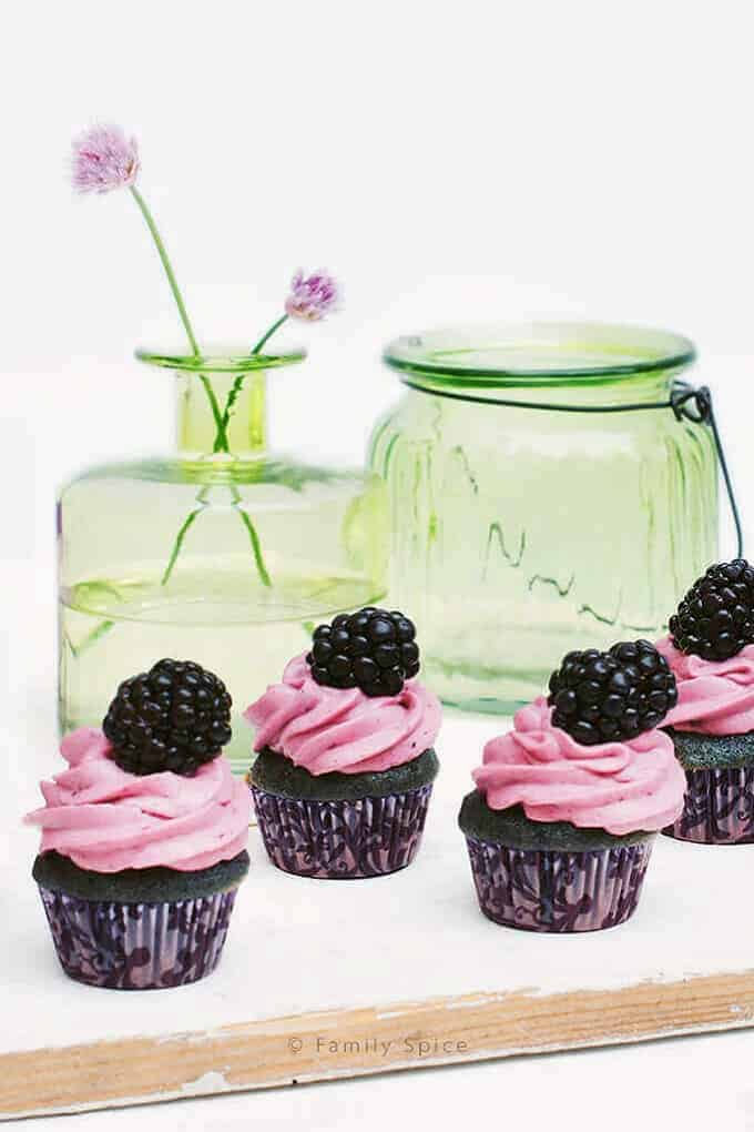 Blackberry and honey cupcakes on a white board with a green jar in the background