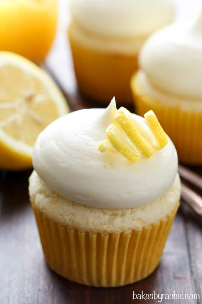 Lemon cupcakes with lemon cream cheese frosting on a wooden board