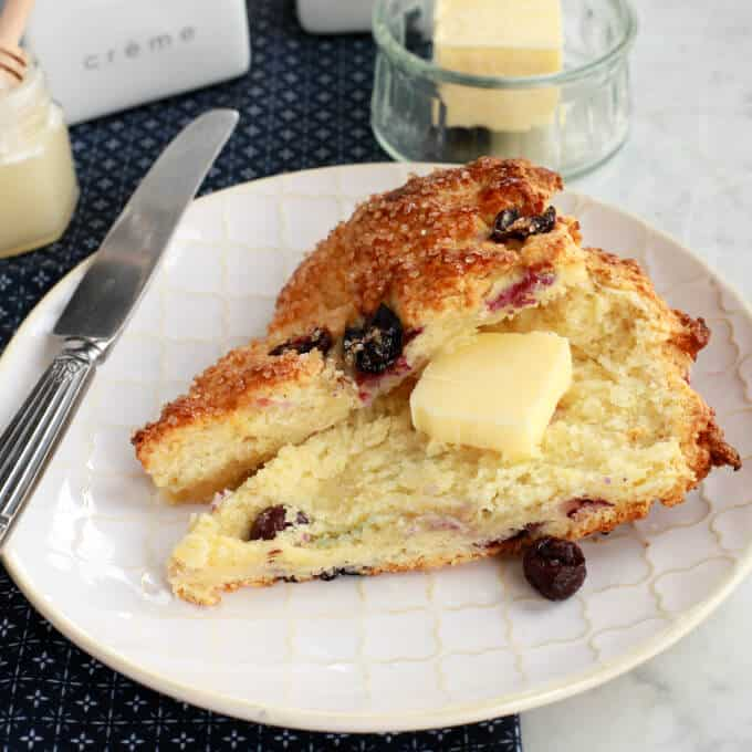 Buttermilk Blueberry Scones - A sliced blueberry scone with a pat of butter on a white plate surrounded by a butter dish, honey, and cream container.