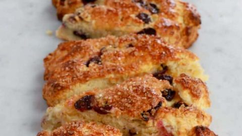 Buttermilk Blueberry Scones - A vertical row of golden baked blueberry scones on a white marble counter.