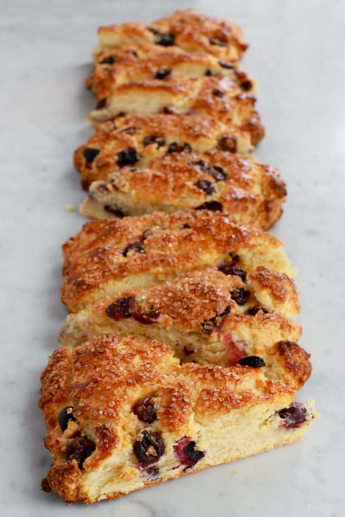 A vertical row of golden baked blueberry scones on a white marble counter.