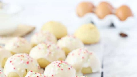 Side view of anise cookies on a baking rack with a white glaze and nonpareils. Eggs in the background