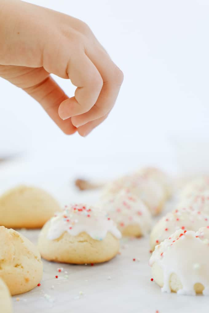Putting sprinkles on top of a cookie