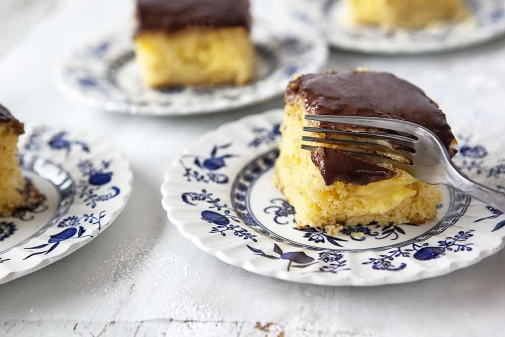Boston Cream Poke Cake - cutting into slice of cake