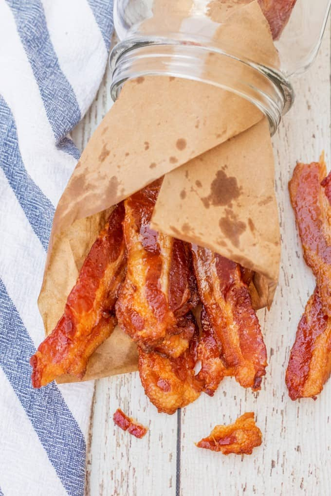Brown Sugar Bacon wrapped in brown paper and stuffed in a jar lying on its side.
