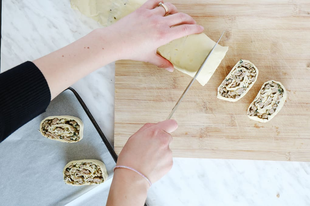 Top view of a hand hold the puff pastry and another cutting pinwheels on a wooden board.