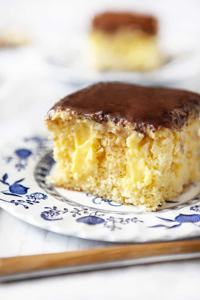 Slice of Boston Cream Poke Cake on antique plate