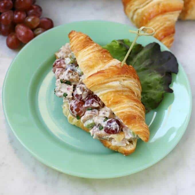 A green plate containing a croissant filled with chicken salad