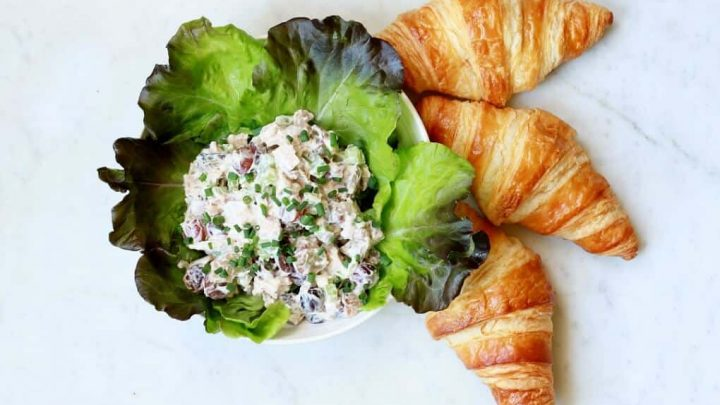 Chicken salad in a lettuce lined bowl with three croissants on a white marble background.