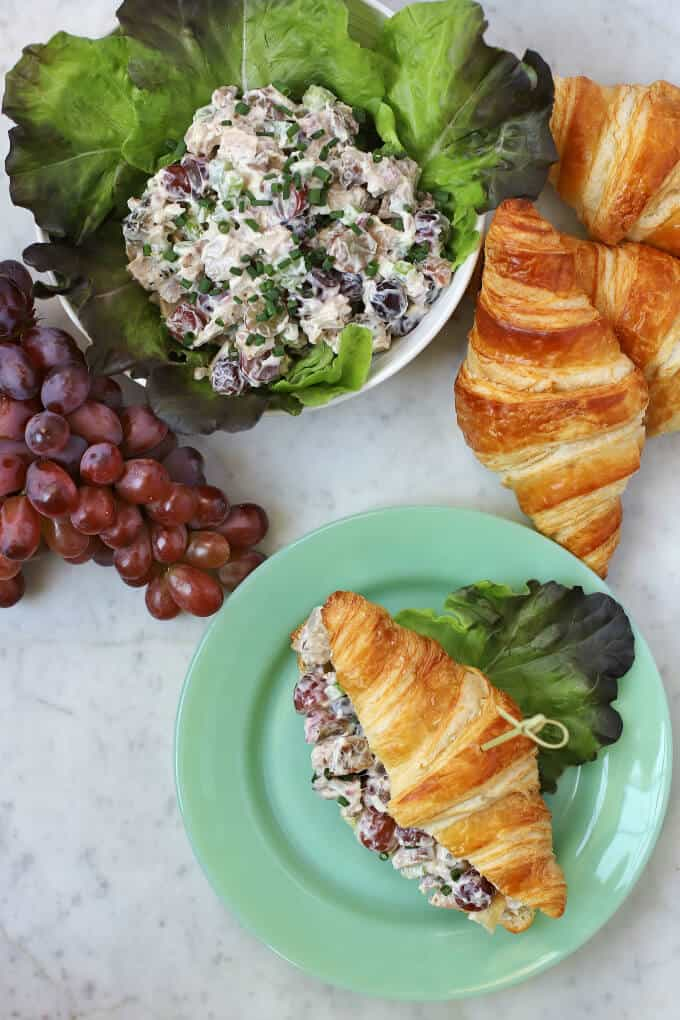 A flat lay on a white marble background containing chicken salad, grapes, and croissants with one filled croissant on a green plate.
