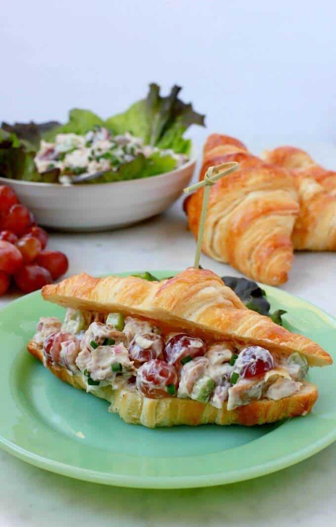 A green plate containing a croissant filled with chicken salad.