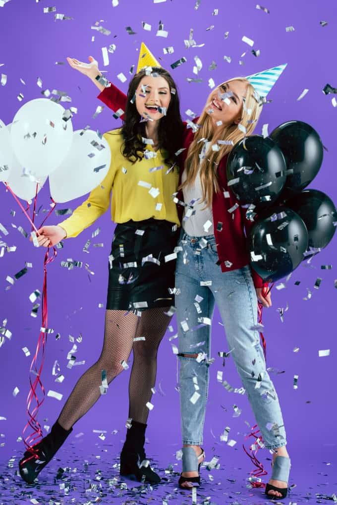 Two teenage girls celebrating a birthday with balloons and confetti