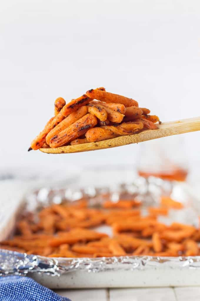 A wooden spoonful of roasted carrots with a baking sheet of carrots in the background