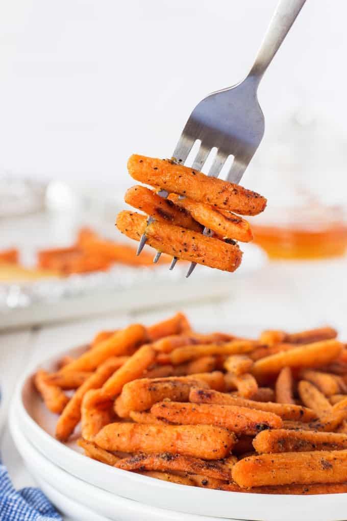 A forkful of carrots from a plate of carrots