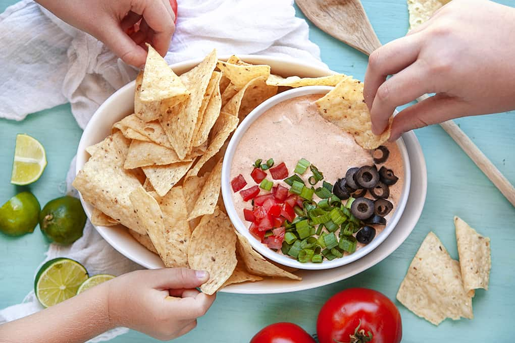 Hands Scooping Mexicali Dip with chips