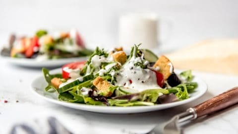 Parmesan peppercorn dressing - A garden salad on a white plate topped with parmesan peppercorn dressing.