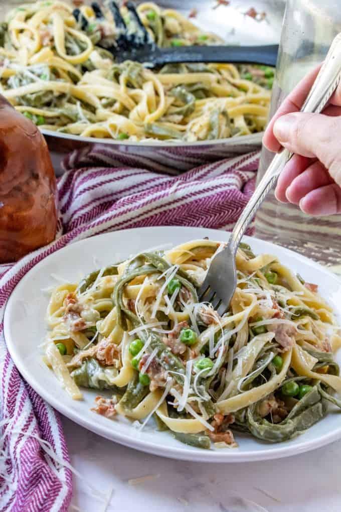 A fork diving into Paglia e Fieno on a white plate