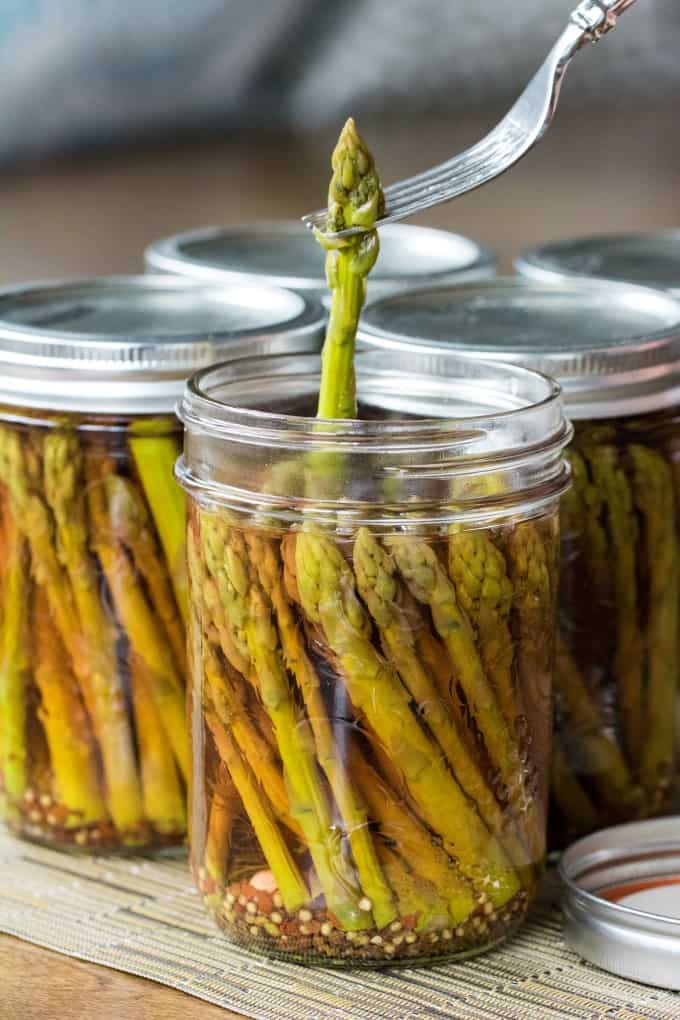 Pulling an asparagus spear out of a jar with a fork