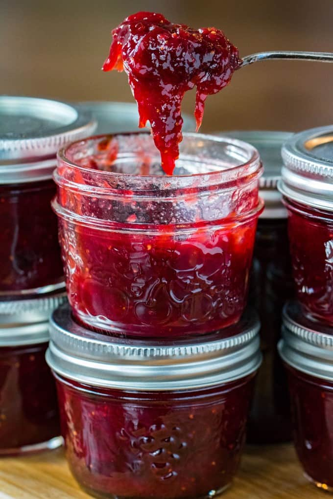 Scooping out ruby red jam from a jar