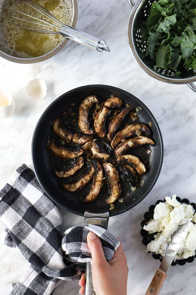 Top view of a cooked mushrooms organized in a spiral in a pan with a hand holding the handle with a dish towel, some fresh kale on the side.