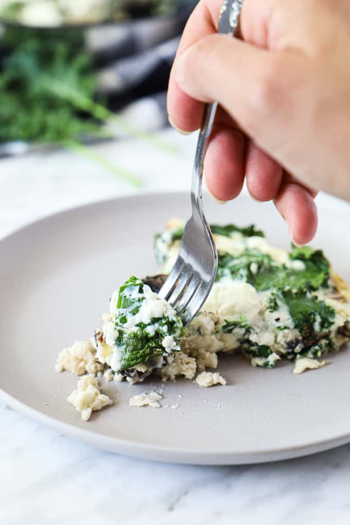 Close up of an egg white frittata in a beige plate with a hand holding a fork